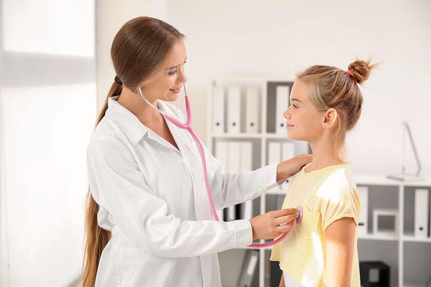 Kardiolog osłuchuje serce dziecka