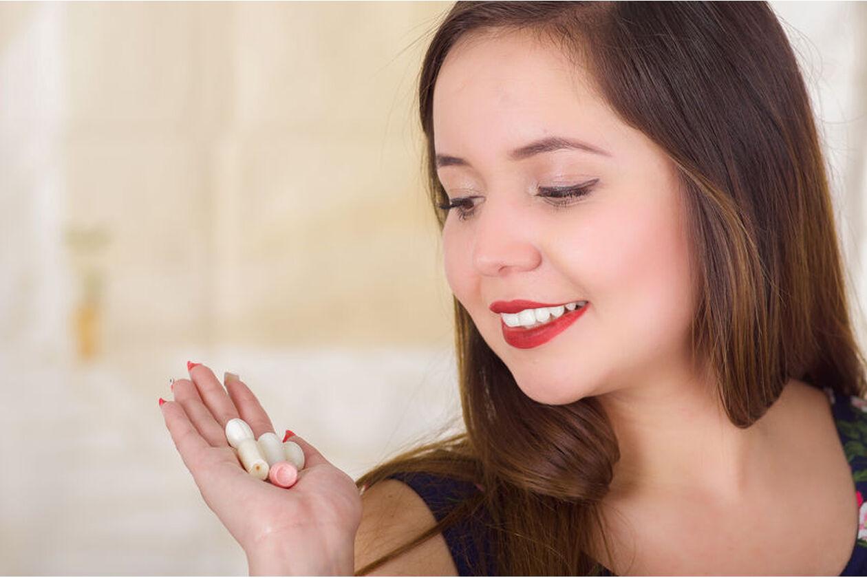 Kobieta trzyma w dłoni globulki z kwasem mlekowym