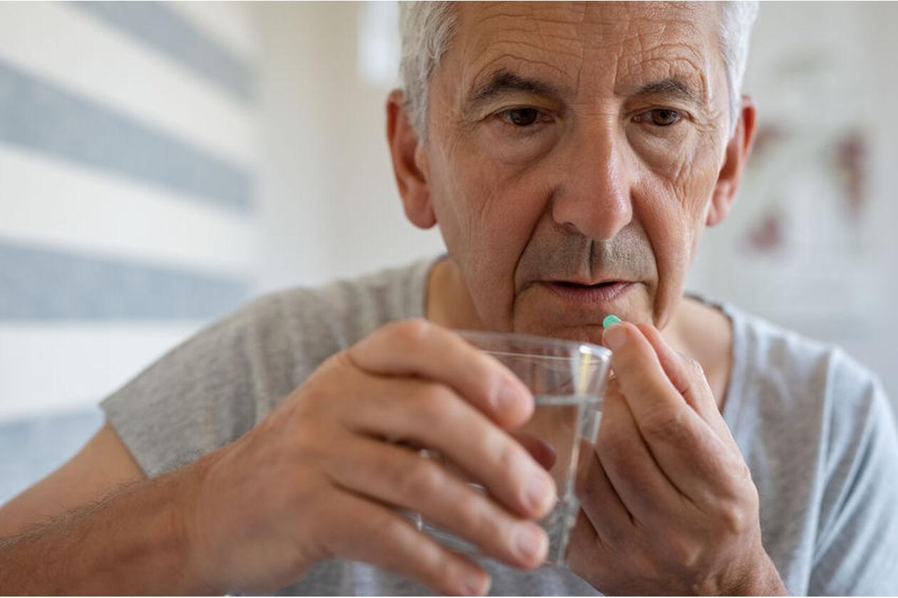 Mężczyzna zażywa tabletkę z amlodypiną