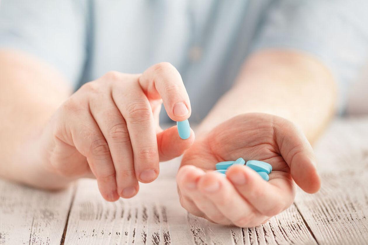 Mężczyzna trzyma w dłoniach tabletki przeciwzapalne