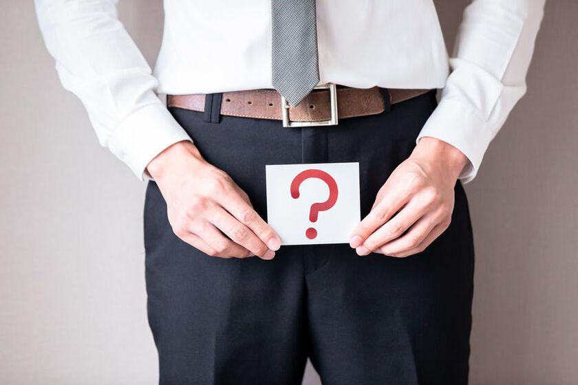Mężczyzna trzyma na kroczku tabliczkę ze znakiem zapytania