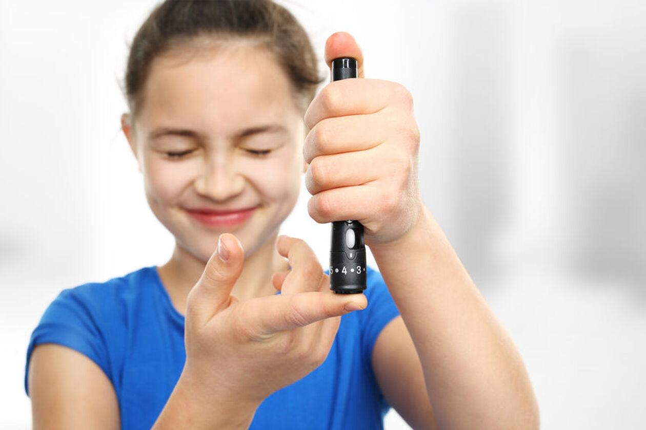 Dziewczynka pobiera próbkę krwi z palca