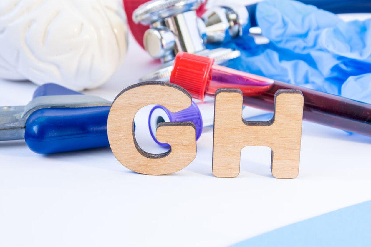 Drewniane literki oznaczające hormon wzrostu i próbka krwi