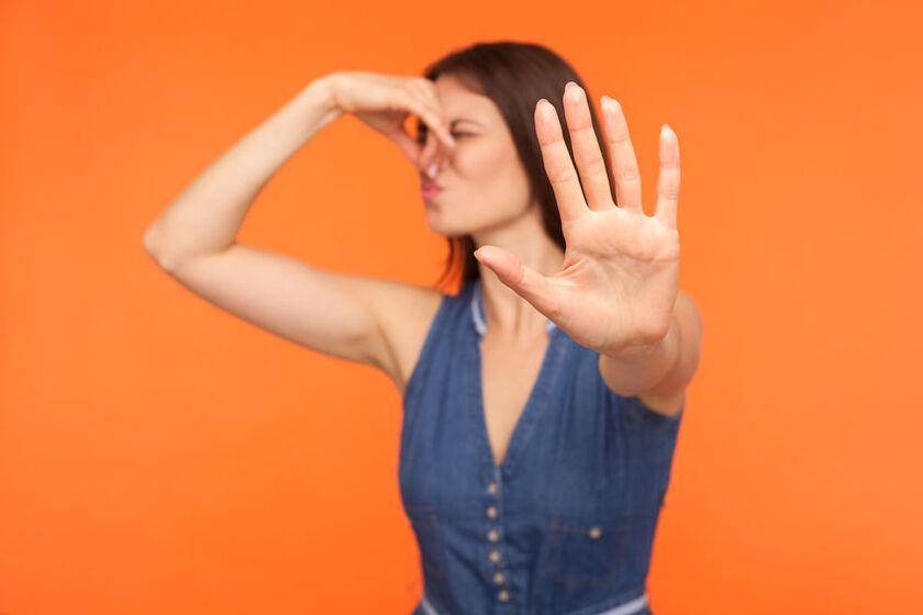 Kobieta zatykająca nos w powodu śmierdzących gazów jelitowych