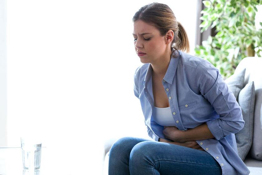 Kobieta cierpi z powodu bólu żołądka i pleców