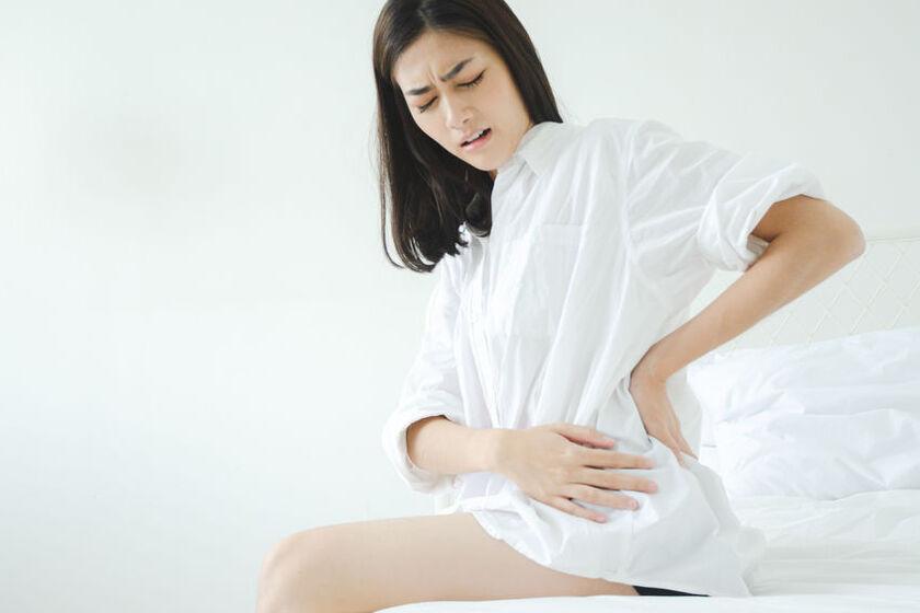 Kobieta trzyma się za brzuch