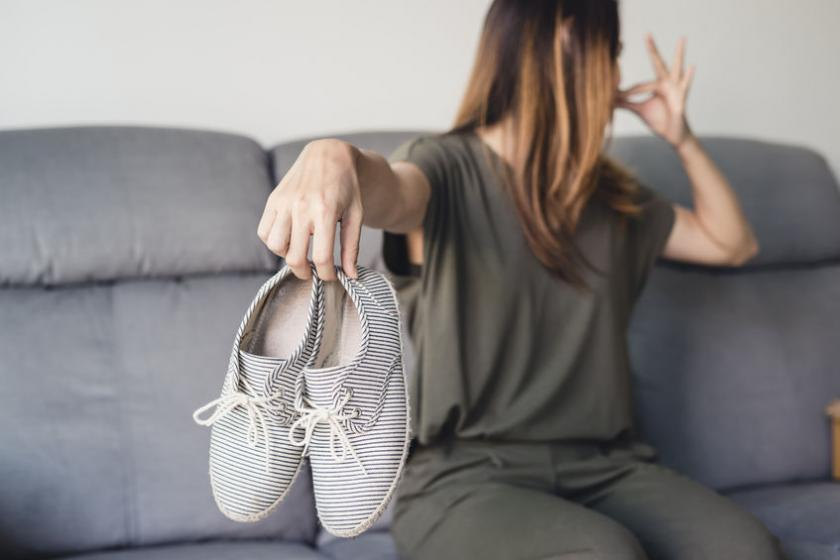 Kobieta trzyma w dłoni brudne buty