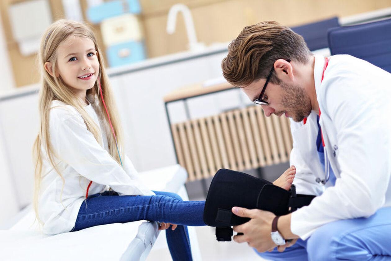 Ortopeda dziecięcy bada dziewczynkę