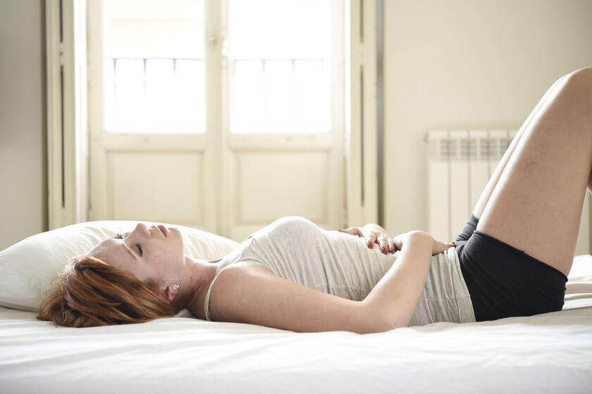 Młoda kobieta trzyma się za brzuch