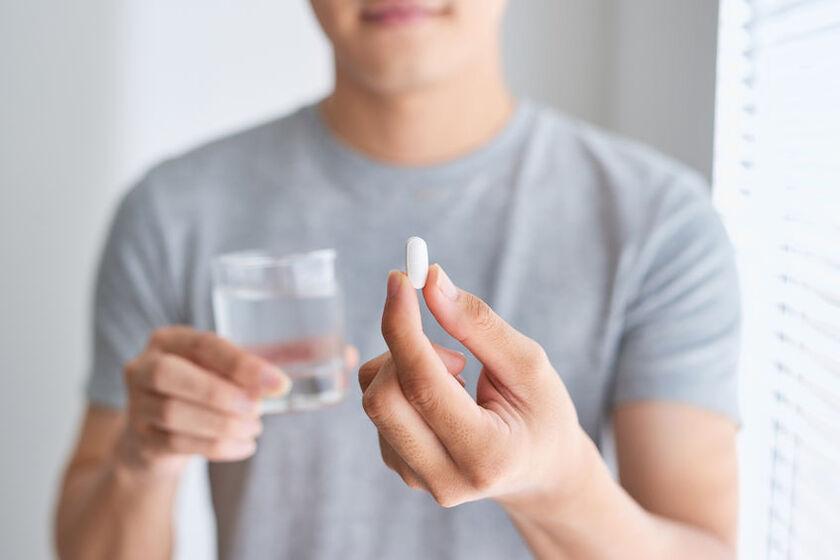 Mężczyzna połyka tabletkę