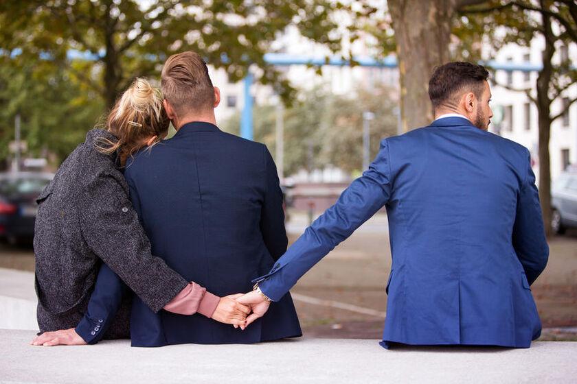 Kobieta przytula mężczyznę a innego trzyma za rękę