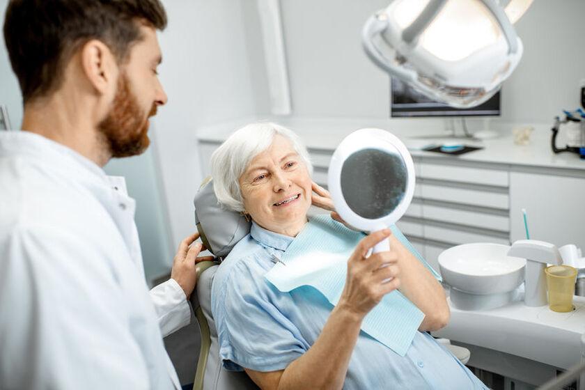 Kobieta ogląda protezę u stomatologa