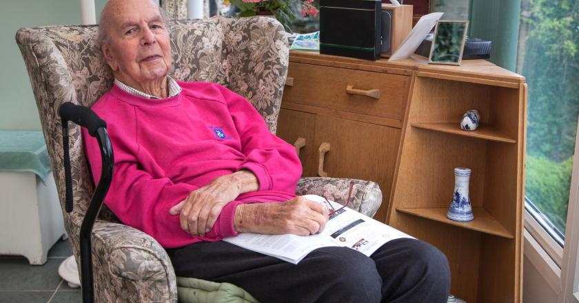 Starszy mężczyzna siedzący w fotelu i czytający gazetę
