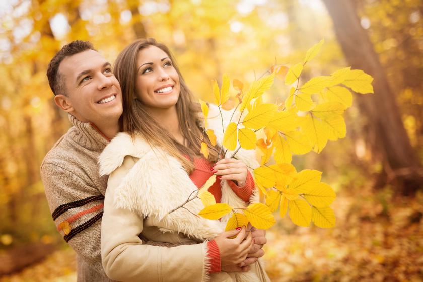 Mężczyzna przytulający kobietę w parku i trzymający jesienne liście