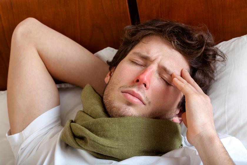 Mężczyzna z zaczerwienionym nosem i szalkiem na szyi leżący w łóżku