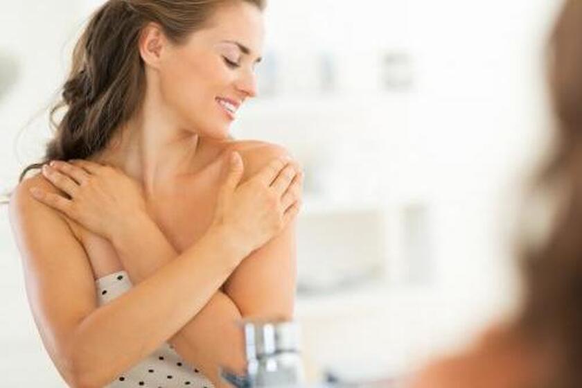 Młoda kobieta masująca swoje ramię