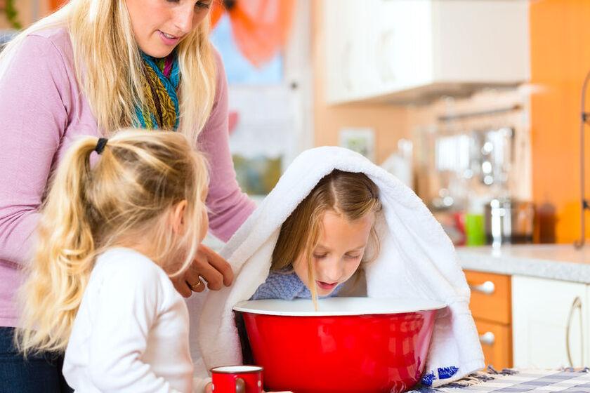 Dziecko z ręcznikiem na głowie, nachylające się nad miską z gorącą wodą