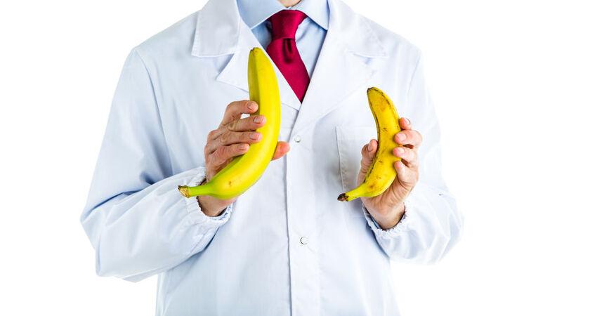Lekarz w białym fartuchu trzymający w dłoniach dwa banany o różnej wielkości