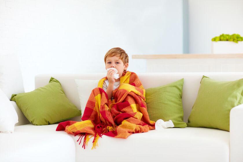 Dziecko siedzące na łóżku, owinięte kocem