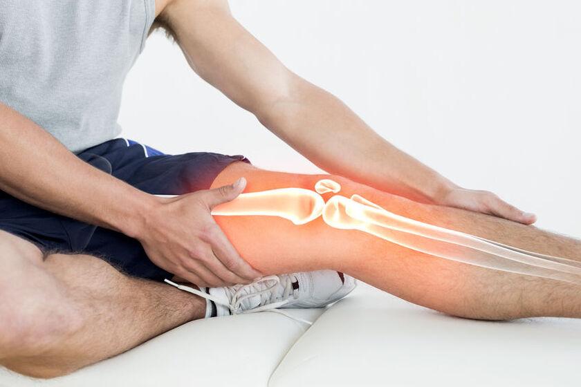 Mężczyzna trzymający dłoń na kolanie