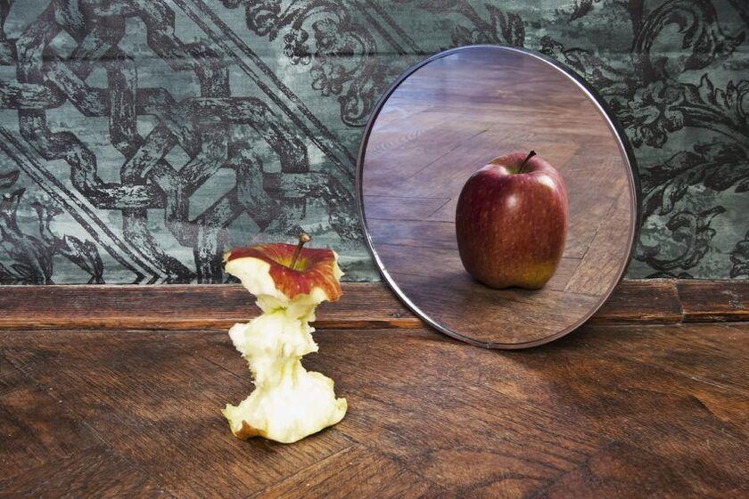 Ogryzek od jabłka stojący przy lustrze