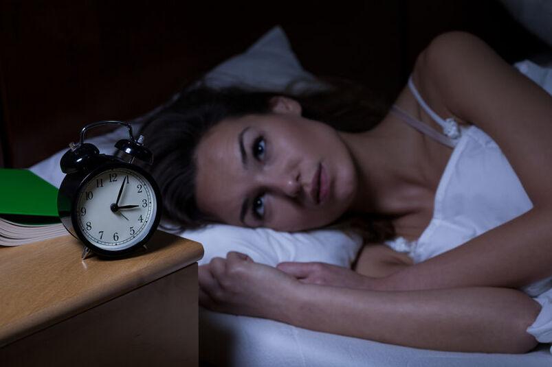 Kobieta leżąca nocą na łóżku i patrząca na zegarek