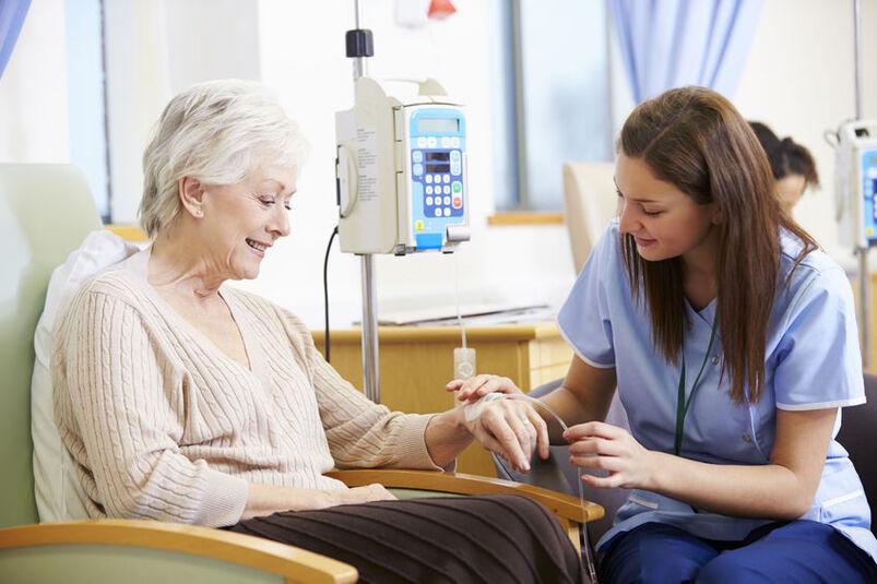 Pielęgniarka siedząca przy starszej kobiecie podczas chemioterapii