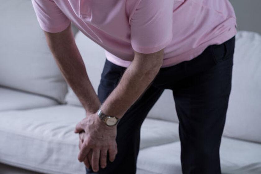 Staraszy mężczyzna trzymający się za kolano