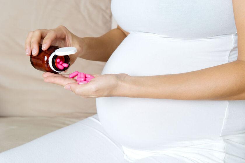 Ciężarna kobieta trzymająca garść tabletek