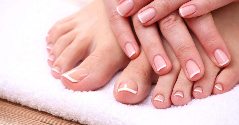Kobieta pokazująca rozdwajające paznokcie i pękające skórki