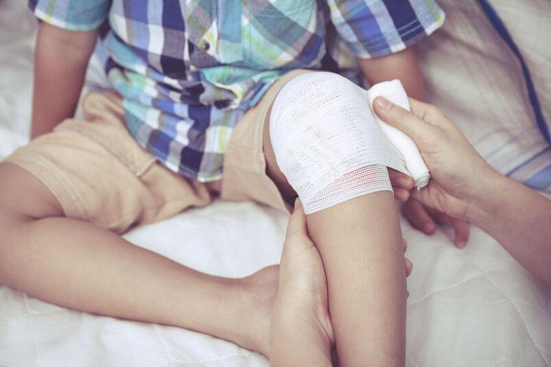 Osoba dorosła zawijająca dziecku opatrunek na kolanie