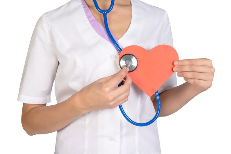 Pielęgniarka w białym fartuchu trzymająca w dłoni papierowe serce i stetoskop