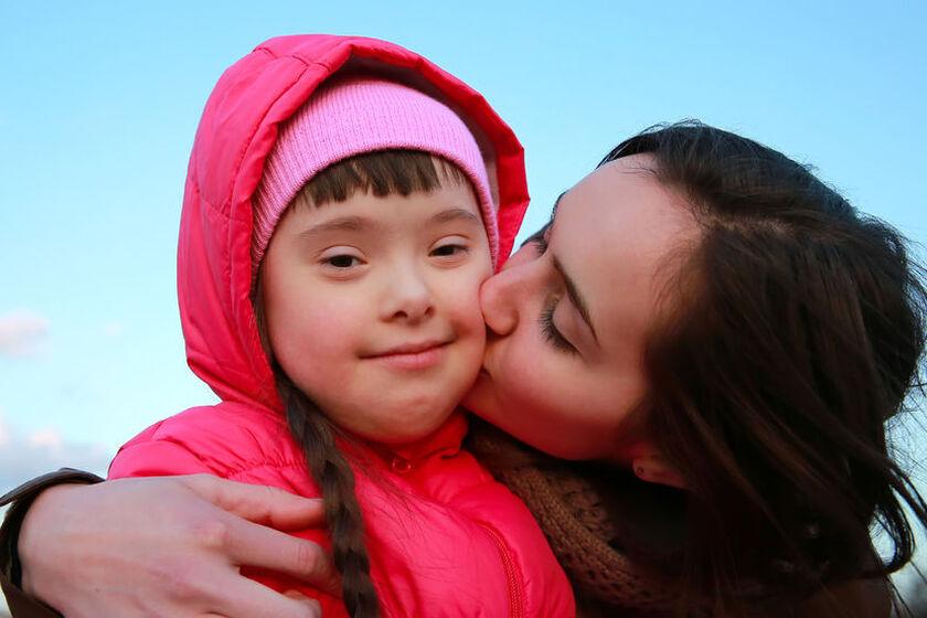 Matka całująca w policzek dziecko z zespołem Downa