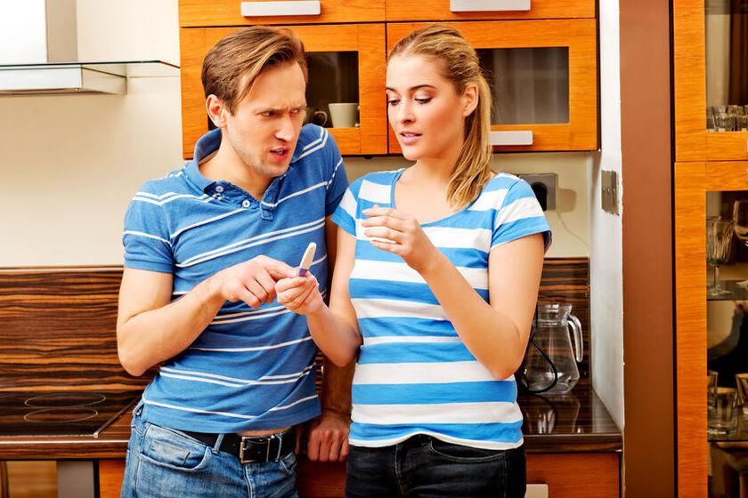 Kobieta i mężczyzna patrzący na wynik testu ciążowego