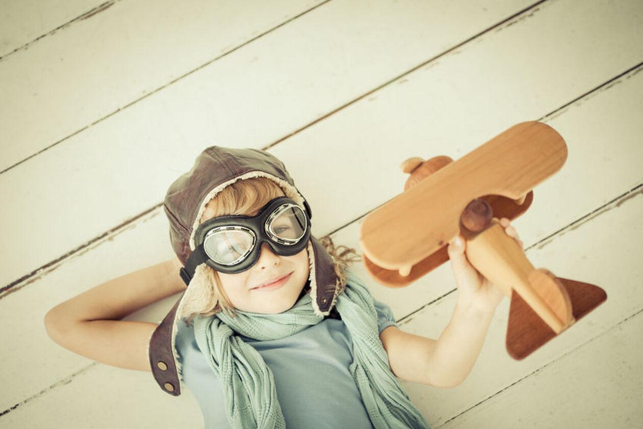 Chłopczyk w czapce pilota z drewnianym samolotem w dłoni