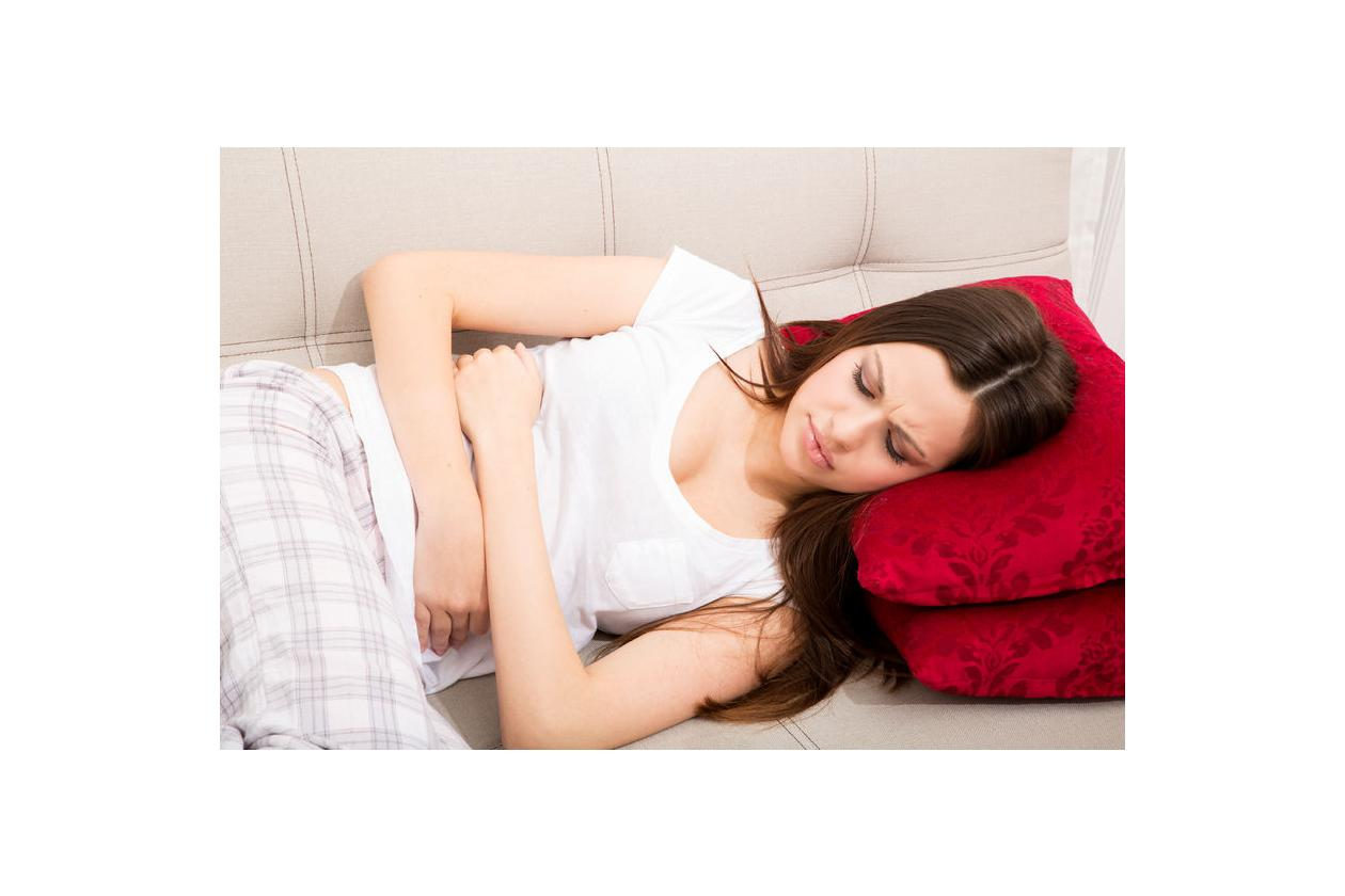 Leżąca kobieta trzymająca się za podbrzusze