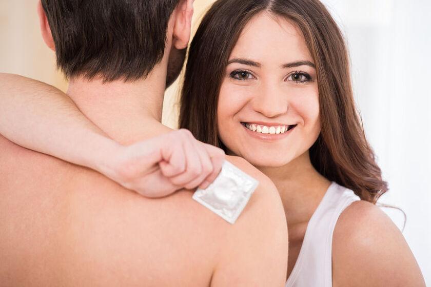 Uśmiechnięta kobieta z prezerwatywą w dłoni