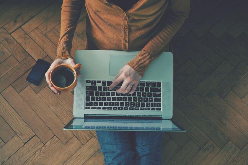 Osoba siedząca przy laptopie z kubkiem kawy