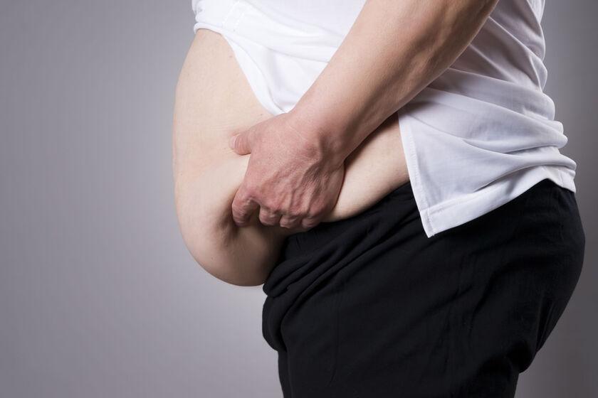 Patologicznie otyły mężczyzna trzymający się za brzuch