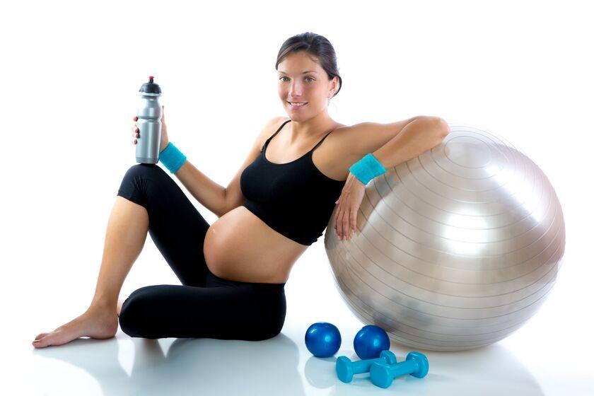 Kobieta w zaawansowanej ciąży siedząca przy piłce do ćwiczeń