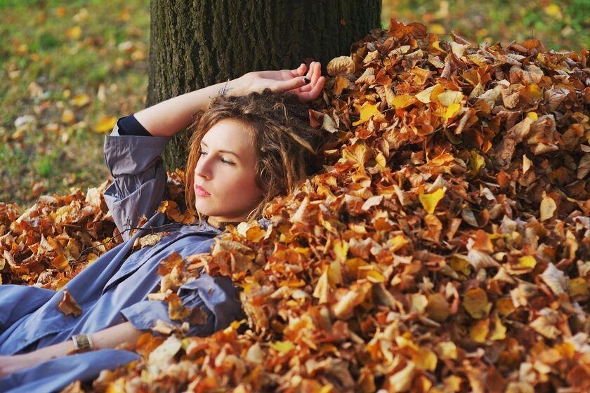 Kobieta leżąca w jesiennych liściach