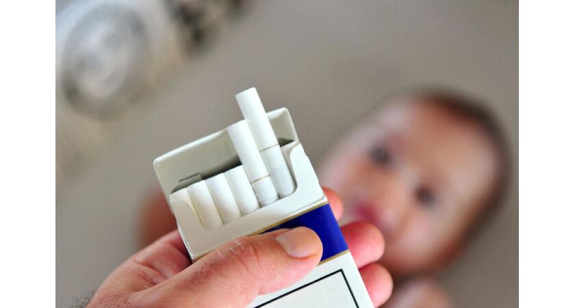 Kobieta trzymająca paczkę papierosów niedaleko dziecka