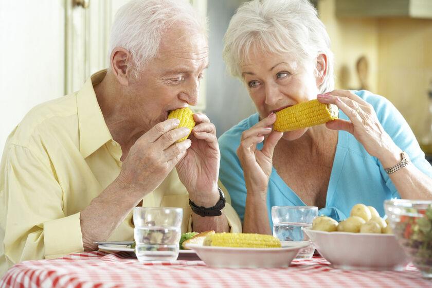 Starsza kobieta i mężczyzna jedzący kolby kukurydzy