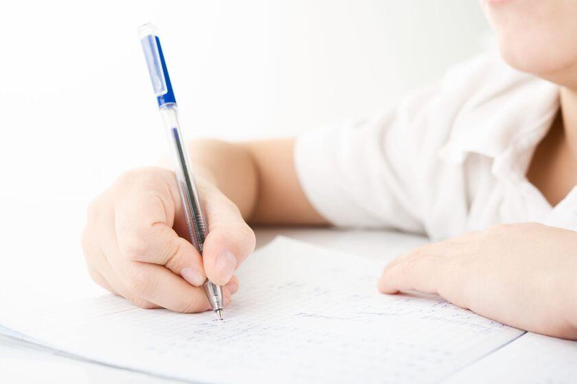 Dziecko piszące długopisem w zeszycie