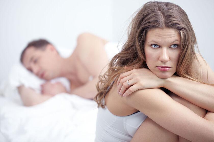 Smutna kobieta i leżący obok mężczyzna