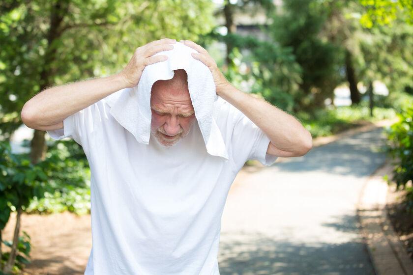 Starszy człowiek walczący z nadmiernym słońcem
