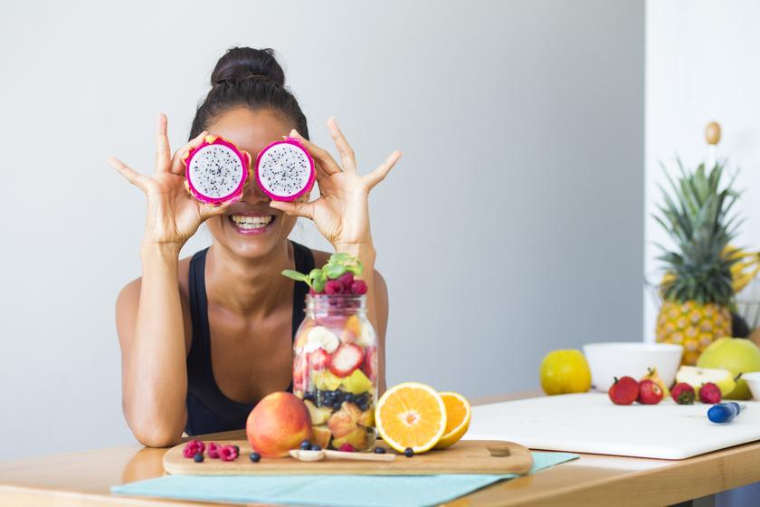 Uśmiechnięta kobieta siedząca przy stole pełnym świeżych owoców