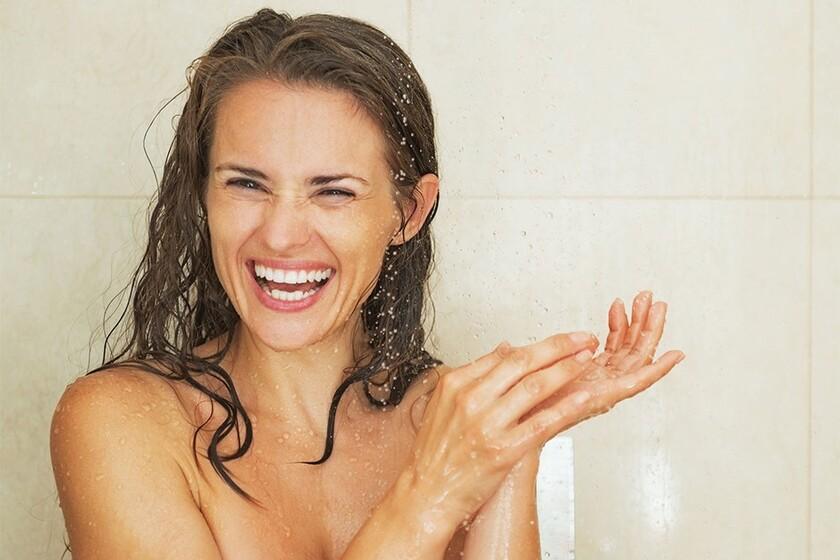 Uśmiechnięta kobieta pod prysznicem