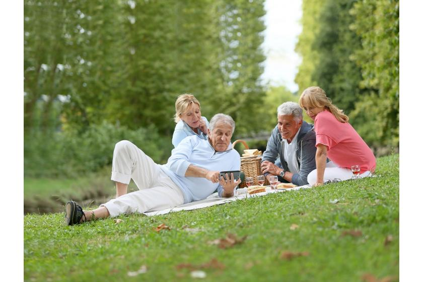 Seniorzy podczas pikniku siedzący na kocu