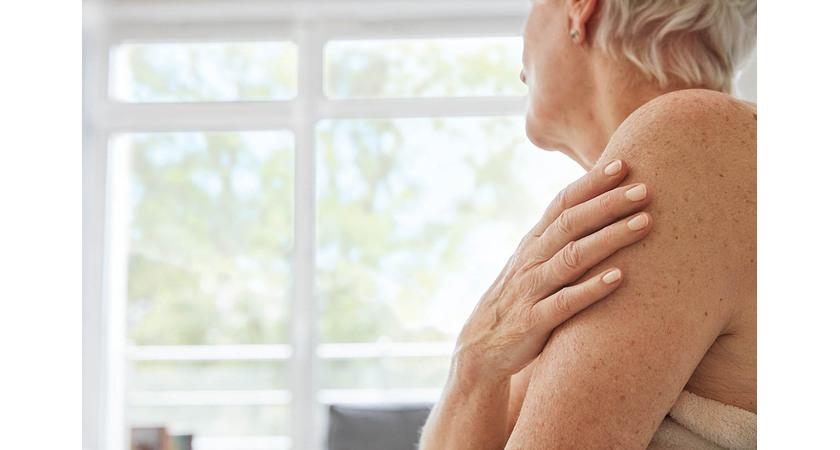 Starsza kobieta trzymająca dłoń na ramieniu